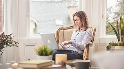 Woman on chair looking at laptop