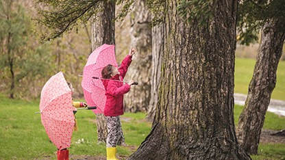Two children holding umbrellas by a tree