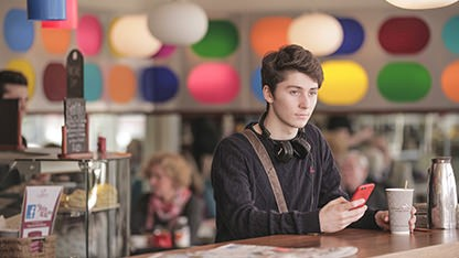 Young guy in restaurant holding a mobile phone