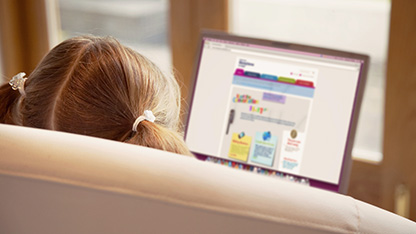 Child looking at moneysense website on a laptop