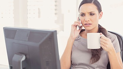 Serious woman on the phone holding a coffee cup