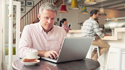older man using laptop in coffee house