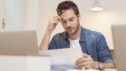 guy looking at document with hand on head