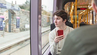 Student holding his mobile phone on the Luas