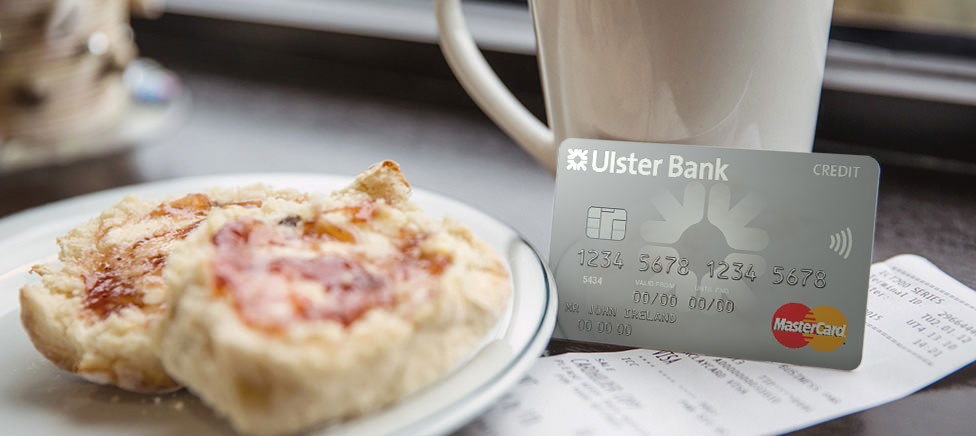 Silver Ulster Bank Credit card covering a receipt for coffee and scones