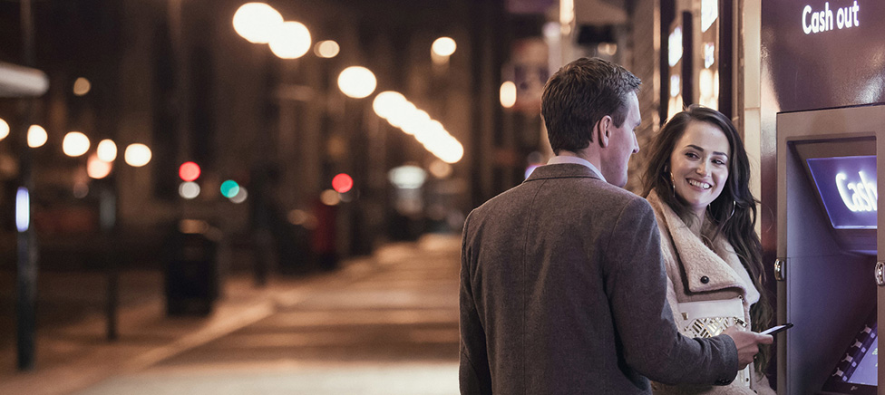 A couple stand in front of an Ulster Bank Cash machine, looking at each other and smiling in a dark street lit by street lights