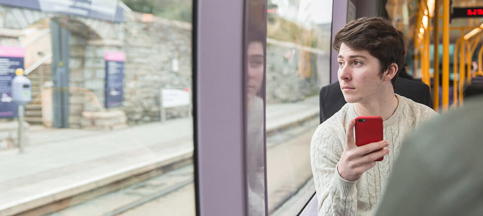 Young guy on a train holding a mobile phone