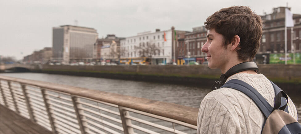 Male student wearing headphones on his neck walking along the Liffey