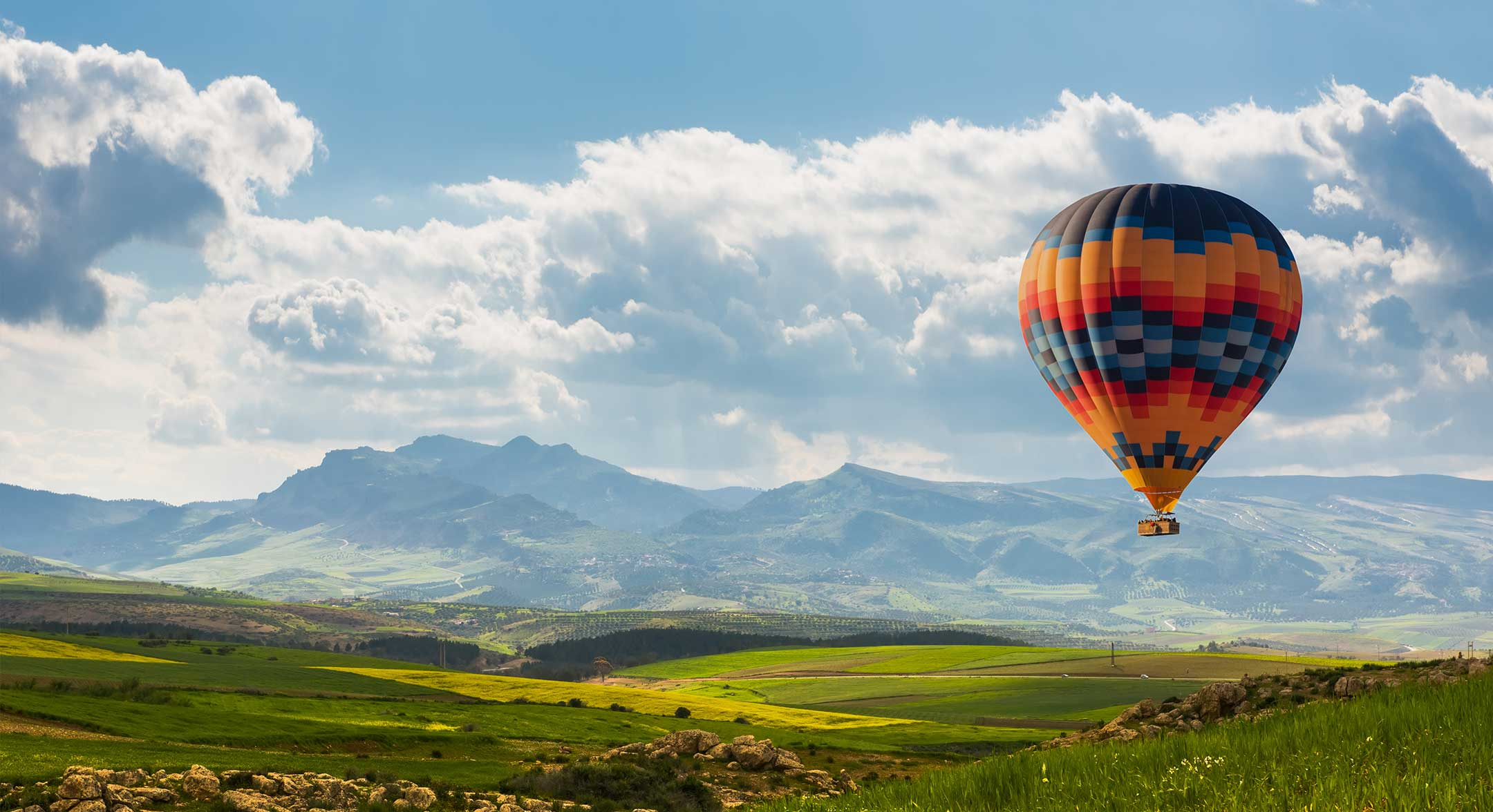 Aztec patterned hot air balloon floating across a blue sky with rolling green hills in the distance